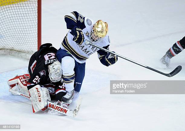 Ryan Faragher of the St Cloud State Huskies covers up the puck as Mario Lucia of the Notre Dame Fighting Irish collides with him during the third...