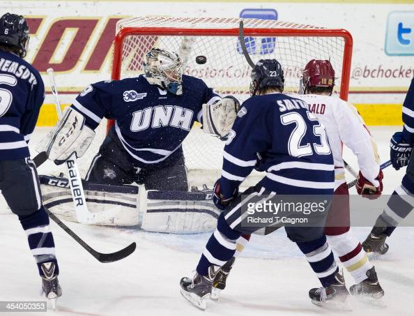 Ryan Fitzgerald of the Boston College Eagles Kyle Smith and Casey DeSmith of the New Hampshire Wildcats watch the puck enter the net on a shot by...