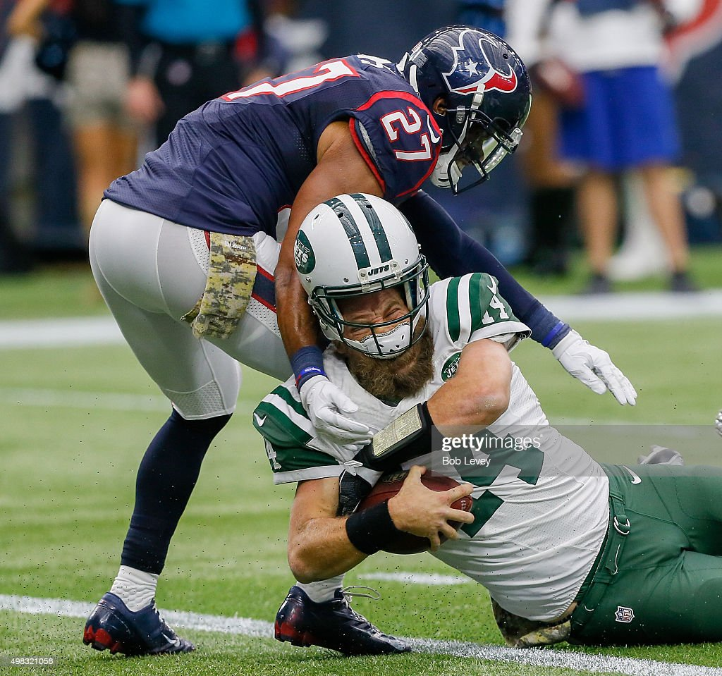 Ryan Fitzpatrick #14 of the New York Jets loses his helmet after taking a hit to the head from Quintin Demps #27 of the Houston Texans in the fourth quarter at NRG Stadium on November 22, 2015 in Houston, Texas.