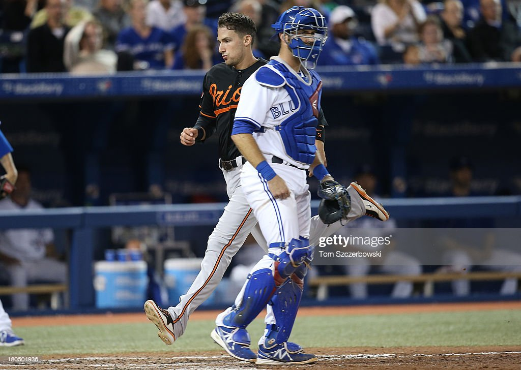 <a gi-track='captionPersonalityLinkClicked' href=/galleries/search?phrase=Ryan+Flaherty&family=editorial&specificpeople=4412528 ng-click='$event.stopPropagation()'>Ryan Flaherty</a> #3 of the Baltimore Orioles comes across home plate to score a run in the seventh inning during MLB game action as <a gi-track='captionPersonalityLinkClicked' href=/galleries/search?phrase=J.P.+Arencibia&family=editorial&specificpeople=4959430 ng-click='$event.stopPropagation()'>J.P. Arencibia</a> #9 of the Toronto Blue Jays looks on on September 13, 2013 at Rogers Centre in Toronto, Ontario, Canada.
