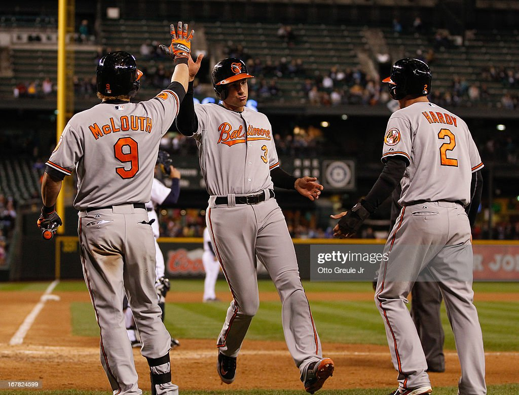 Ryan Flaherty #3 of the Baltimore Orioles is congratulated by <a gi-track='captionPersonalityLinkClicked' href=/galleries/search?phrase=Nate+McLouth&family=editorial&specificpeople=536572 ng-click='$event.stopPropagation()'>Nate McLouth</a> #9 and J.J. Hardy #2 as he scores in the sixth inning against the Seattle Mariners at Safeco Field on April 30, 2013 in Seattle, Washington.