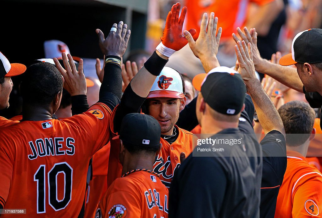 Ryan Flaherty #3 of the Baltimore Orioles is greeted in the dugout by teammates after hitting a three home run in the third inning against the New York Yankees at Oriole Park at Camden Yards on June 29, 2013 in Baltimore, Maryland.