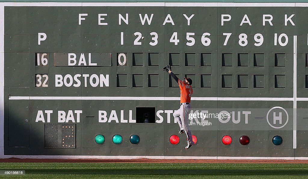 Ryan Flaherty #3 of the Baltimore Orioles leaps to make a catch on a ball hit by Xander Bogaerts #2 of the Boston Red Sox in the first inning at Fenway Park on September 26, 2015 in Boston, Massachusetts.