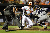 Ryan Flaherty of the Baltimore Orioles scores a run against Christian Bethancourt of the San Diego Padres on a single hit by Hyun Soo Kim of the...