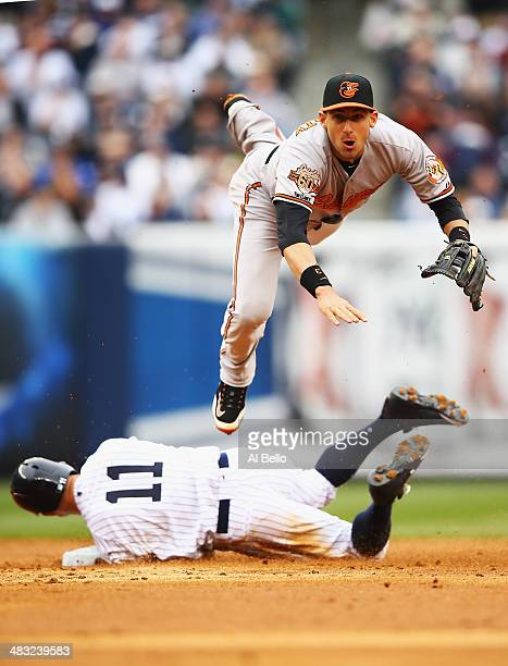 Ryan Flaherty of the Baltimore Orioles turns a double play as Brett Gardner of the New York Yankees slides in the third inning against the Baltimore...