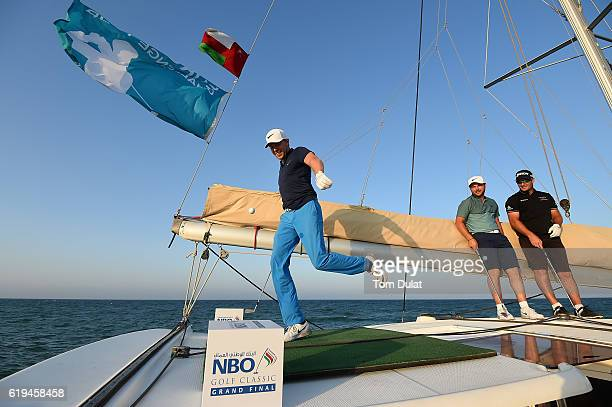 Ryan Fox of New Zealand and Jordan Smith of England watch Alexander Knappe of Germany kick a ball from the boat at Al Mouj during previews of the NBO...