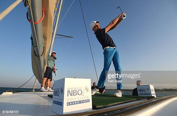 Ryan Fox of New Zealand and Jordan Smith of England watch Alexander Knappe of Germany hit a ball from the boat at Al Mouj during previews of the NBO...