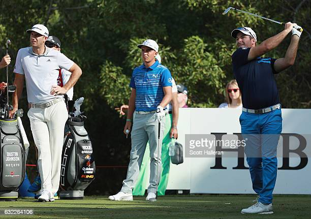 Ryan Fox of New Zealand hits his tee shot on the fourth hole as Rickie Fowler of the United States and Dustin Johnson of the United States look on...