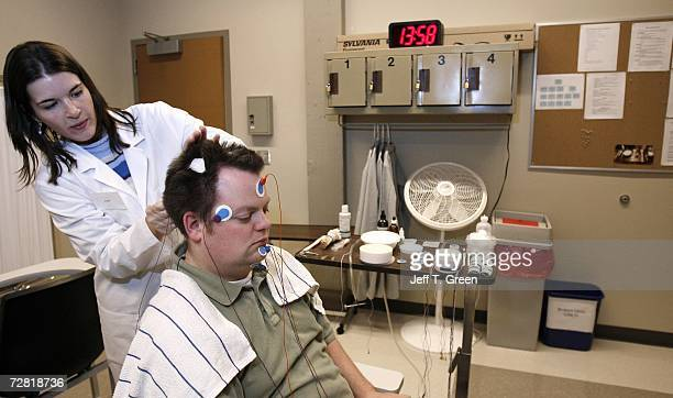 Ryan Gamble has wires applied to his head by lab technologist Amy Bender in preparation for a polysomnographic recording system demonstration at...