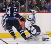 Ryan Garbutt of the Dallas Stars gets tripped up as he battles with Grant Clitsome of the Winnipeg Jets for the puck in second period action of an...
