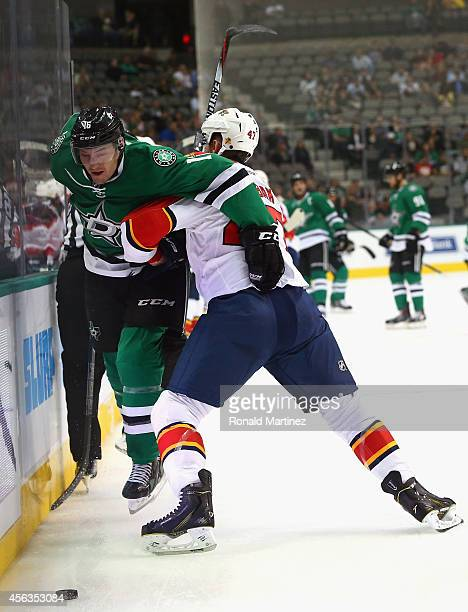 Ryan Garbutt of the Dallas Stars skates the puck against Colby Robak of the Florida Panthers during a preseason game at American Airlines Center on...