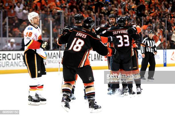 Ryan Getzlaf is congratuated by Jakob Silfverberg and Patrick Eaves of the Anaheim Ducks as Matt Stajan of the Calgary Flames skates past after...