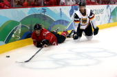Ryan Getzlaf of Canada fights for the puck against Sven Felski of Germany during the ice hockey Men's Qualification Playoff game between Germany and...
