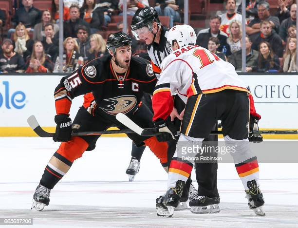 Ryan Getzlaf of the Anaheim Ducks and Mikael Backlund of the Calgary Flames talk with referee Brad Watson before a faceoff during the third period of...