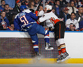 Ryan Getzlaf of the Anaheim Ducks checks Frans Nielsen of the New York Islanders during the first period at the Nassau Veterans Memorial Coliseum on...