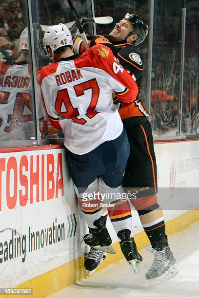 Ryan Getzlaf of the Anaheim Ducks collides into Colby Robak of the Florida Panthers along the boards on November 16 2014 at Honda Center in Anaheim...
