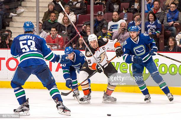 Ryan Getzlaf of the Anaheim Ducks is checked by Sven Baertschi as the stick of Bo Horvat of the Vancouver Canucks goes flying during their NHL game...