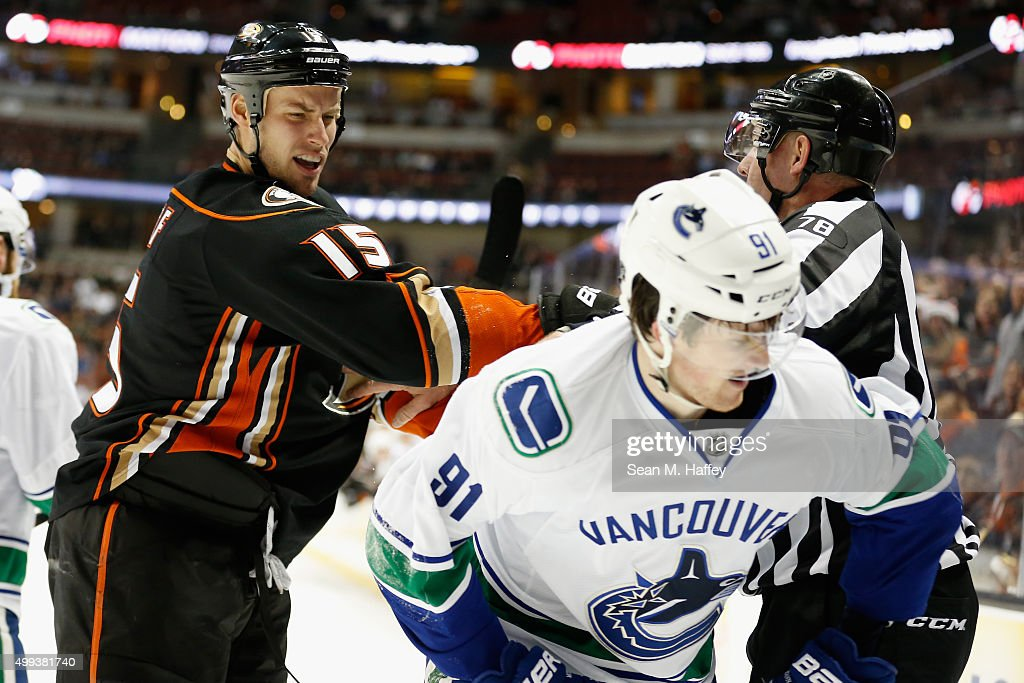 Ryan Getzlaf #15 of the Anaheim Ducks is restrained by linesman Brian Mach #78 as he hits Jared McCann #91 of the Vancouver Canucks during the third period of a game at Honda Center on November 30, 2015 in Anaheim, California.