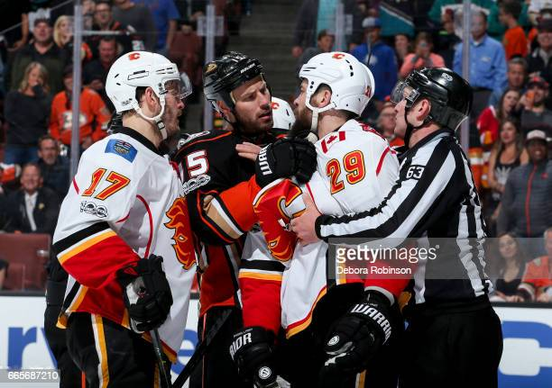 Ryan Getzlaf of the Anaheim Ducks is separated from Lance Bouma and Deryk Engelland of the Calgary Flames by linesman Trent Knorr during the third...