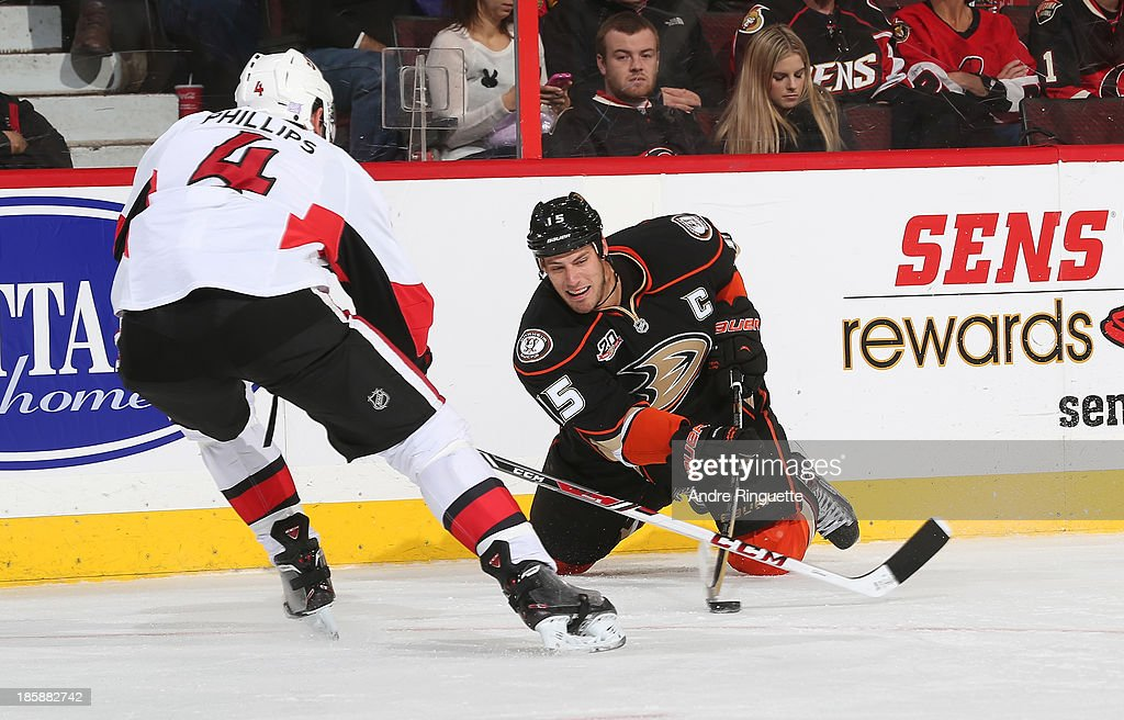 <a gi-track='captionPersonalityLinkClicked' href=/galleries/search?phrase=Ryan+Getzlaf&family=editorial&specificpeople=602655 ng-click='$event.stopPropagation()'>Ryan Getzlaf</a> #15 of the Anaheim Ducks looks to pass the puck from his knees against Chris Phillips #4 of the Ottawa Senators at Canadian Tire Centre on October 25, 2013 in Ottawa, Ontario, Canada.