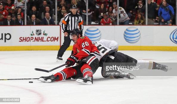 Ryan Getzlaf of the Anaheim Ducks takes down Brandon Saad of the Chicago Blackhawks at the United Center on December 6 2013 in Chicago Illinois The...
