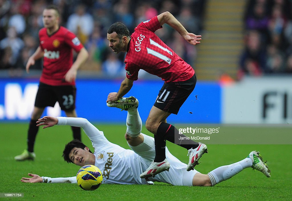 Ryan Giggs of Manchester United battles with Ki Sung-Yueng of Swansea City during the Barclays Premier League match between Swansea City and Manchester United at the Liberty Stadium on December 23, 2012 in Swansea, Wales.