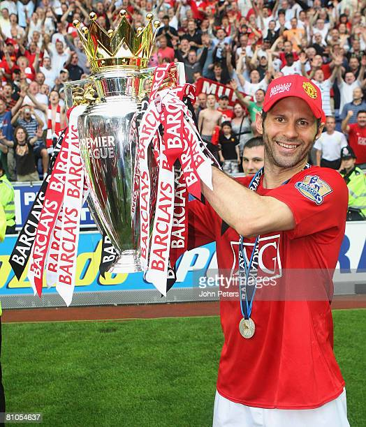 Ryan Giggs of Manchester United celebrates with the Premier League trophy on the pitch after the Barclays FA Premier League match between Wigan...