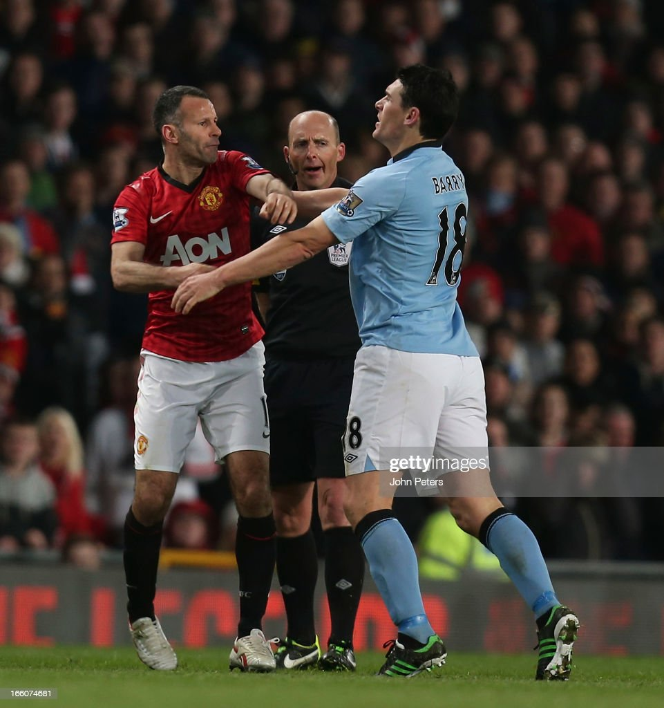 Ryan Giggs of Manchester United clashes with Gareth Barry of Manchester City during the Barclays Premier League match between Manchester United and Manchester City at Old Trafford on April 8, 2013 in Manchester, England.
