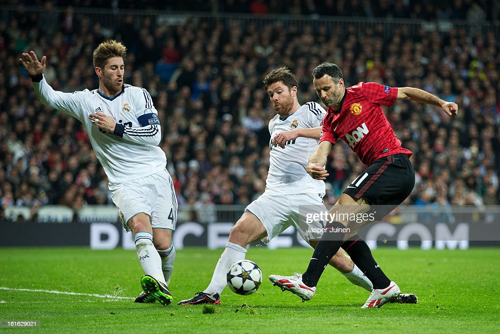 Ryan Giggs (R) of Manchester United shoots on goal past Xabi Alonso (C) and Sergio Ramos of Real Madrid during the UEFA Champions League Round of 16 first leg match between Real Madrid and Manchester United at Estadio Santiago Bernabeu on February 13, 2013 in Madrid, Spain.