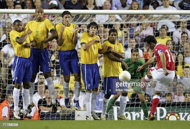 Ryan Giggs of Wales sees his freekick blocked by the Brazilian wall consisting of Julio Baptista Anderson Silva Edmilson Kaka and Ronaldinho during...