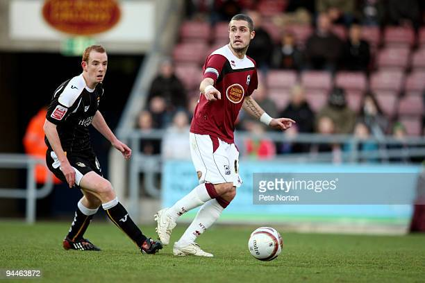 Ryan Gilligan of Northampton Town looks to play the ball watched byTommy Fraser of Port Vale during the Coca Cola League Two Match between...