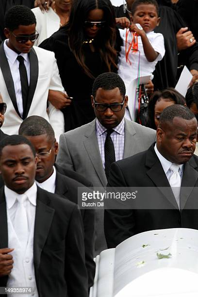 Ryan Glover in grey suit walks behind the casket as it is carried to the carriage with Tameka Foster and Naviyd Raymond behind him after the funeral...