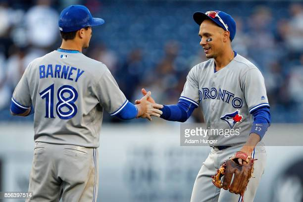 Ryan Goins of the Toronto Blue Jays and Darwin Barney of the Blue Jays celebrate after defeating the New York Yankees at Yankee Stadium on October 1...