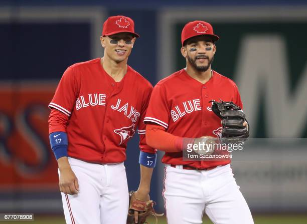 Ryan Goins of the Toronto Blue Jays and Devon Travis talk during a break in the action during their MLB game against the Tampa Bay Rays at Rogers...