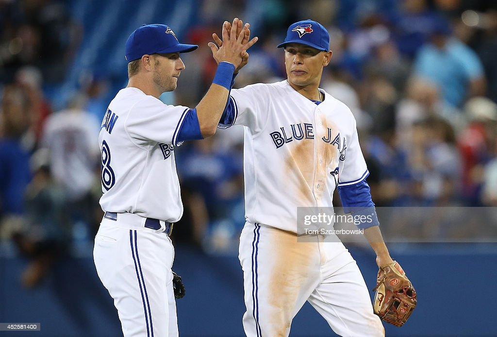 <a gi-track='captionPersonalityLinkClicked' href=/galleries/search?phrase=Ryan+Goins&family=editorial&specificpeople=9004043 ng-click='$event.stopPropagation()'>Ryan Goins</a> #17 of the Toronto Blue Jays celebrates their victory with Steve Tolleson #18 during MLB game action against the Boston Red Sox on July 23, 2014 at Rogers Centre in Toronto, Ontario, Canada.