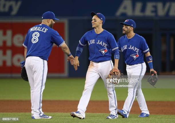 Ryan Goins of the Toronto Blue Jays celebrates their victory with Kendrys Morales and Devon Travis during MLB game action against the Cincinnati Reds...