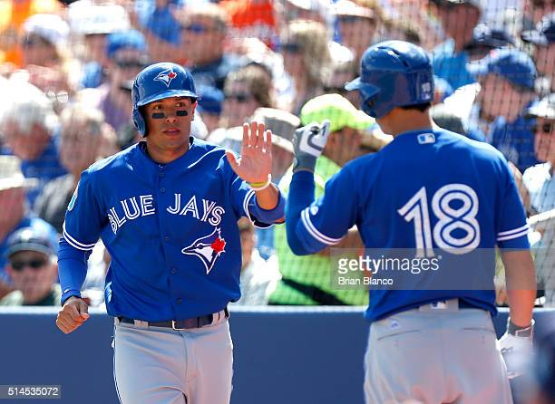 Ryan Goins of the Toronto Blue Jays celebrates with teammate Darwin Barney after scoring off of a wild pitch during the first inning of an MLB spring...