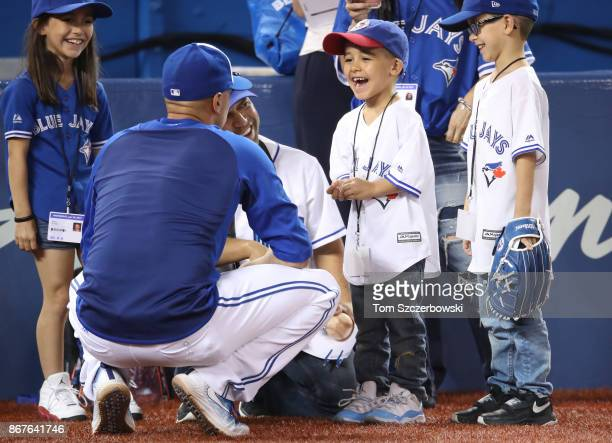 Ryan Goins of the Toronto Blue Jays greets young fans during batting practice before the start of MLB game action against the Oakland Athletics at...