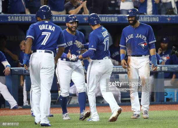 Ryan Goins of the Toronto Blue Jays is congratulated by Kevin Pillar and Jose Bautista after hitting a grand slam home run in the sixth inning during...