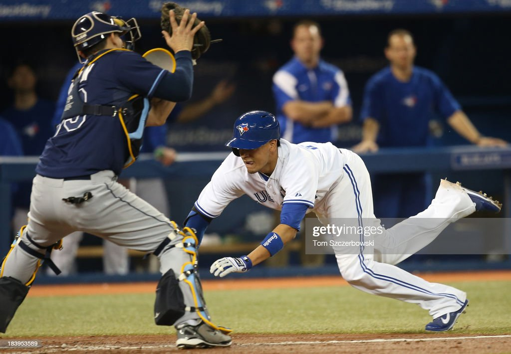 Ryan Goins #17 of the Toronto Blue Jays is tagged out at home plate following his RBI single in the fourth inning during MLB game action by Jose Lobaton #59 of the Tampa Bay Rays on September 27, 2013 at Rogers Centre in Toronto, Ontario, Canada.