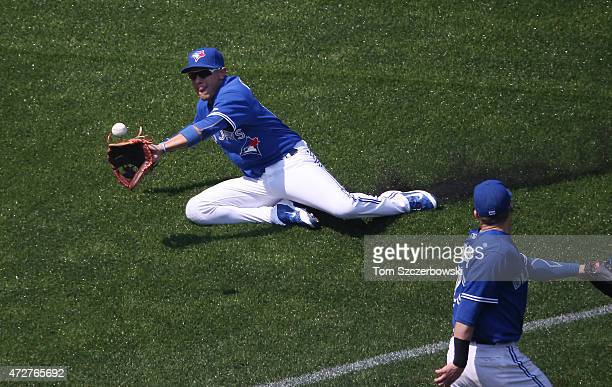 Ryan Goins of the Toronto Blue Jays makes a sliding catch in the fourth inning during MLB game action against the Boston Red Sox on May 9 2015 at...
