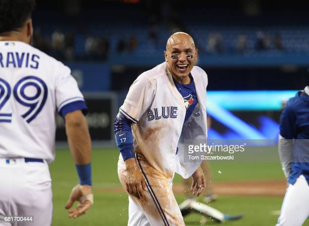 Ryan Goins of the Toronto Blue Jays reacts after being doused by Devon Travis after his gamewinning RBI single in the ninth inning during MLB game...