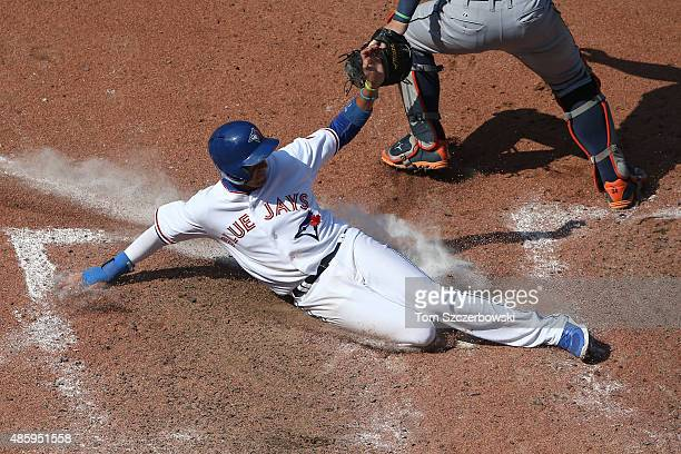 Ryan Goins of the Toronto Blue Jays slides across home plate safely to score a run on an RBI single by Josh Donaldson in the eighth inning during MLB...