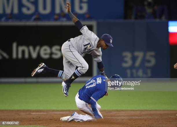 Ryan Goins of the Toronto Blue Jays slides safely into second base in the third inning during MLB game action as Tim Beckham of the Tampa Bay Rays...