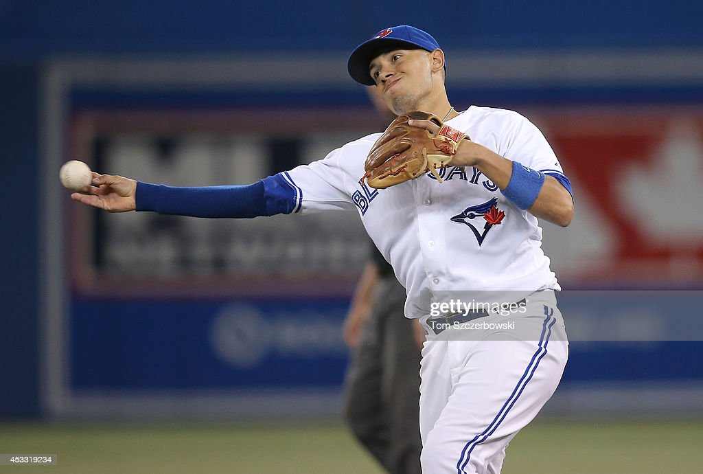 Ryan Goins #17 of the Toronto Blue Jays throws out the baserunner in the seventh inning during MLB game action against the Baltimore Orioles on August 7, 2014 at Rogers Centre in Toronto, Ontario, Canada.