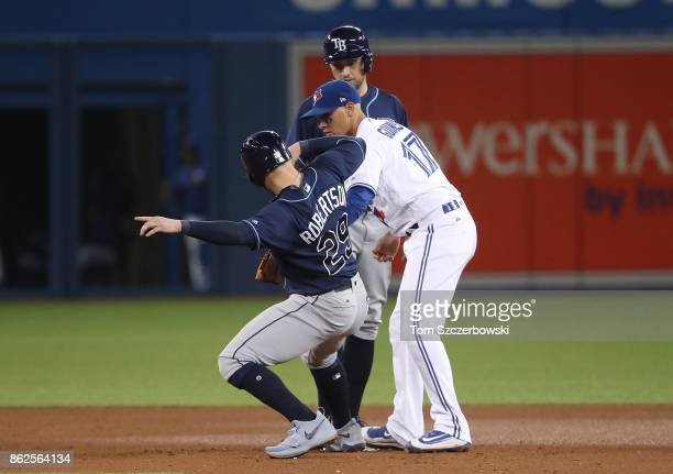 Ryan Goins of the Toronto Blue Jays turns a double play at second base which would be reversed upon video replay review in the seventh inning during...