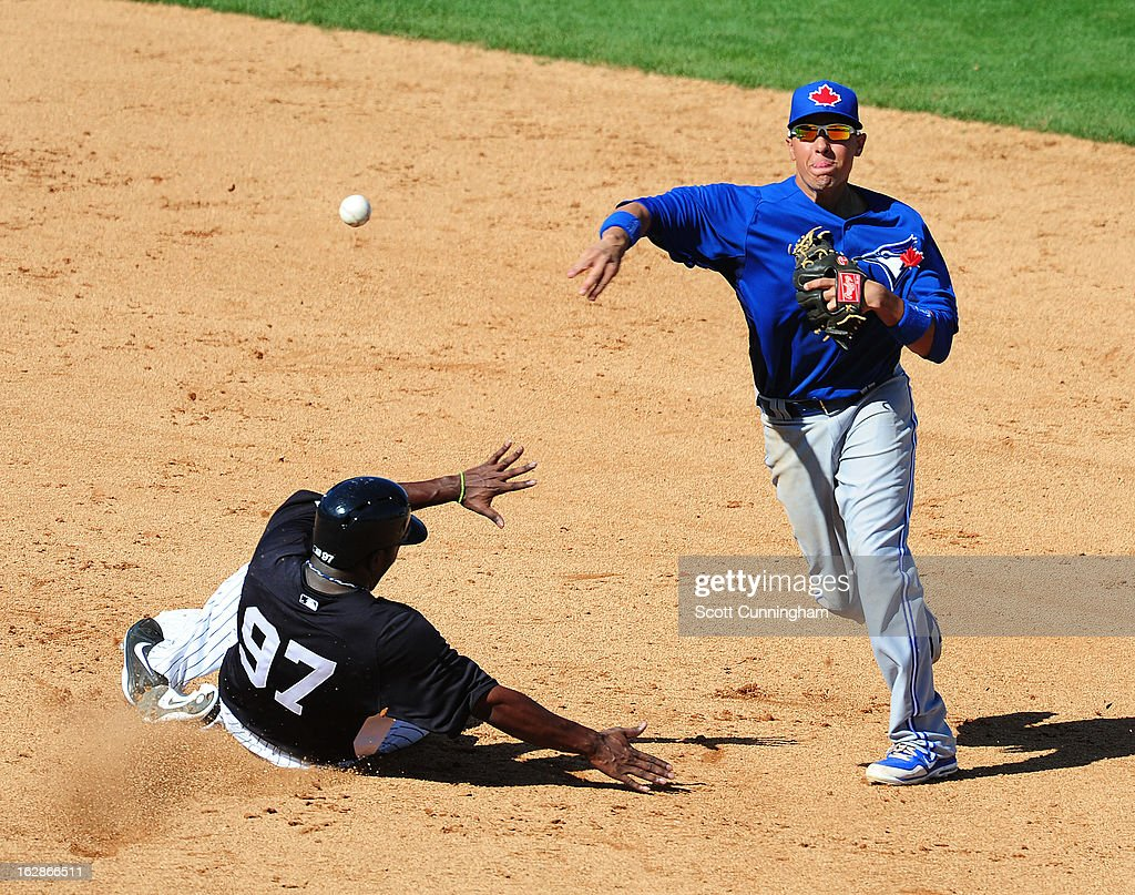 Ryan Goins #2 of the Toronto Blue Jays turns a double play during the spring training game against Jose Pirela #97 of the New York Yankees at George M. Steinbrenner Field on February 28, 2013 in Tampa, Florida.