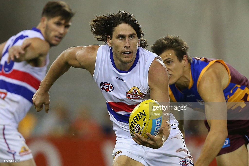 Ryan Griffin of the Bulldogs handballs during the round 22 AFL match between the Brisbane Lions and the Western Bulldogs at The Gabba on August 25, 2013 in Brisbane, Australia.