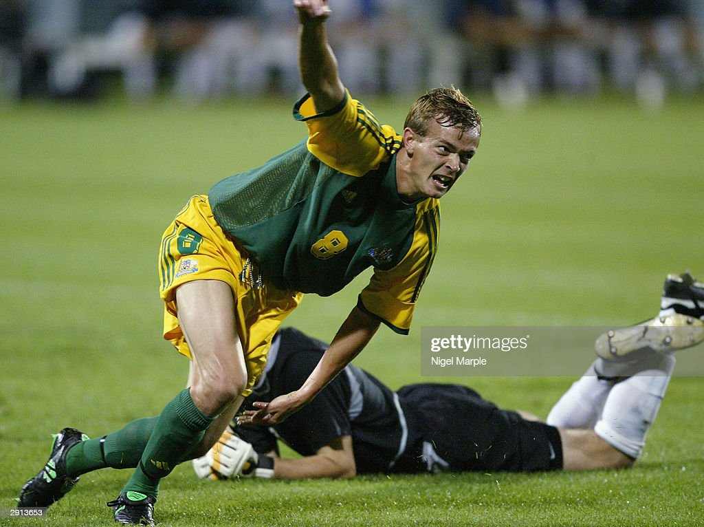 Ryan Griffiths of Australia celebrates scoring his goal as goalkeeper Glen Moss#1 of New Zealand lies on the ground during the Olympic Qualifying...