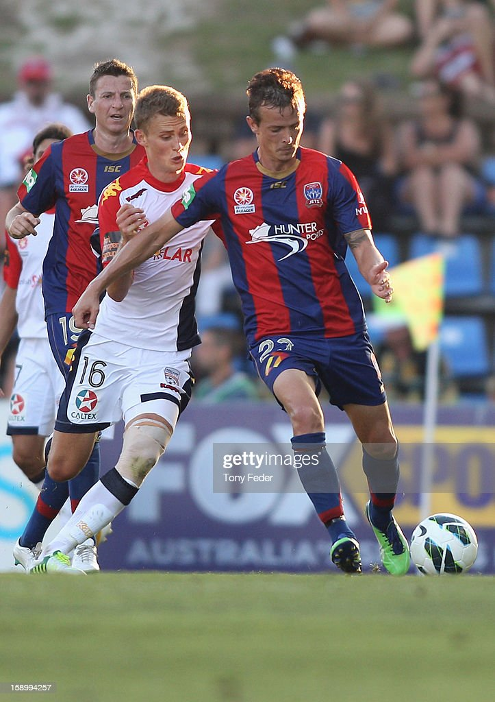 Ryan Griffiths of the Jets and Daniel Bowles of Adelaide contest the ball during the round 15 A-League match between the Newcastle Jets and Adelaide United at Hunter Stadium on January 5, 2013 in Newcastle, Australia.